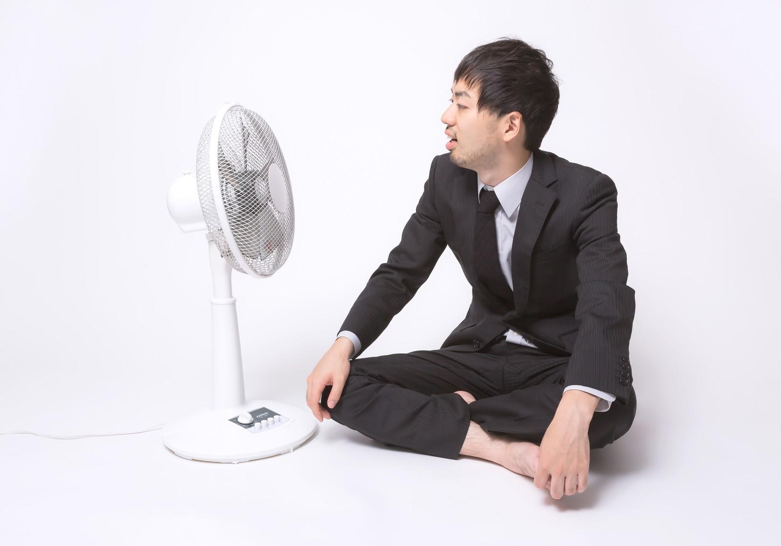 扇風機の前でくつろぐ男性