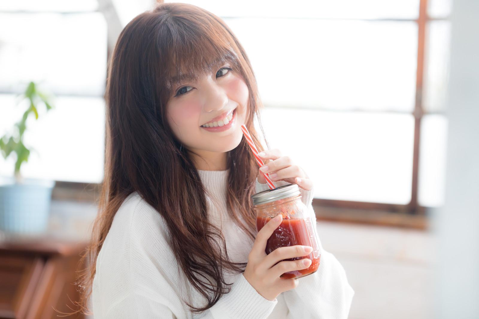 赤いスムージーを飲む女子